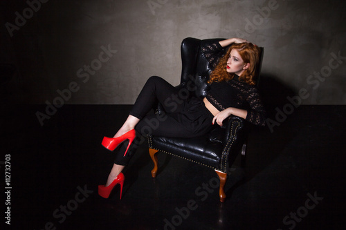 Model In High Heels Sitting On Black Chair Buy This Stock Photo