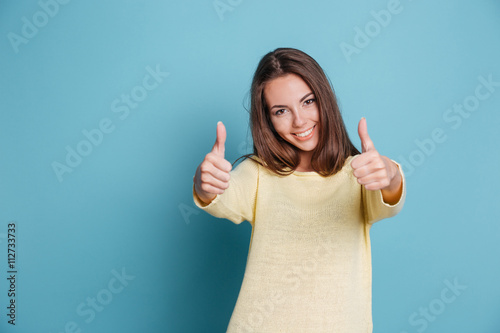 Beautiful woman giving thumbs up over blue background