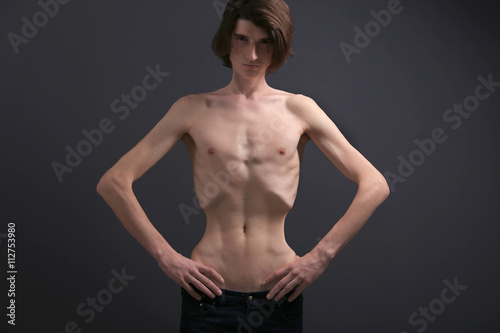 Skinny young man with anorexia on dark background Canvas Print