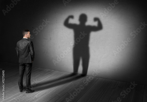 Fotografía  Back view of businessman looks to shadow with strong his display in future