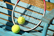 Tennis balls and racket on a blue background