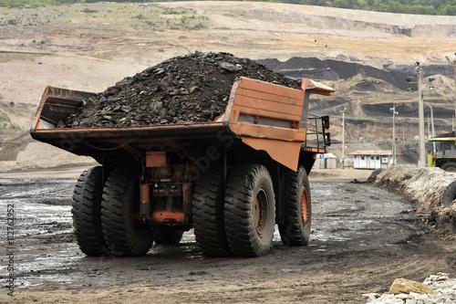 Plakat Żółta koparka ładuje ziemię na ciężarówce przy kopalni z powrotem zaświeca