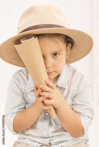 3c2be5b7af930 Adorable little girl in a safari hat and explorer clothes hiding her face  behind treasure map
