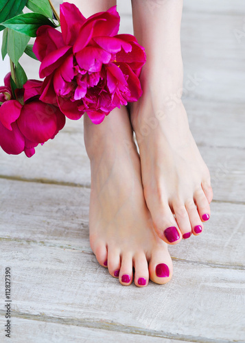 Feet with pink pedicure and peonies Canvas Print