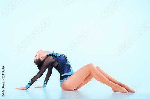 Papiers peints Gymnastique The girl doing gymnastics dance on a blue background