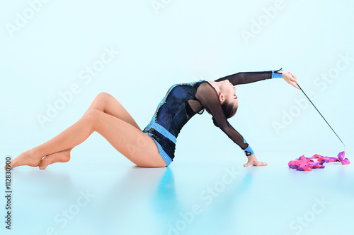 Tuinposter Gymnastiek The girl doing gymnastics dance with colored ribbon on a blue background