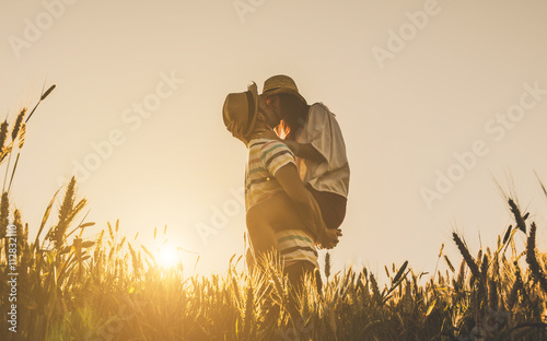 Fotografie, Obraz  Young couple kissing on the background of a sunset in the wheat field