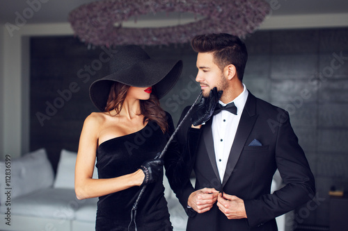 Sensual woman in black hat and whip with lover плакат