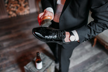 Cleaning Shoes On Wooden Background. Black Shoe With A Brush