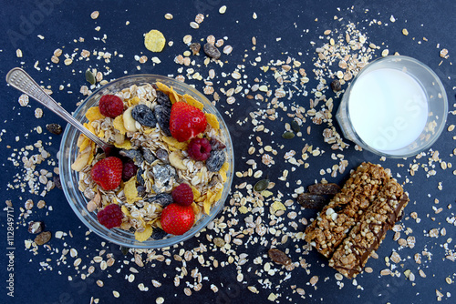Muesli with milk, nuts and berries for breakfast diet on a dark background