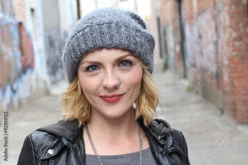Fotografia  Young modern urban girl with blond hair in front of graffiti walls smiling frien