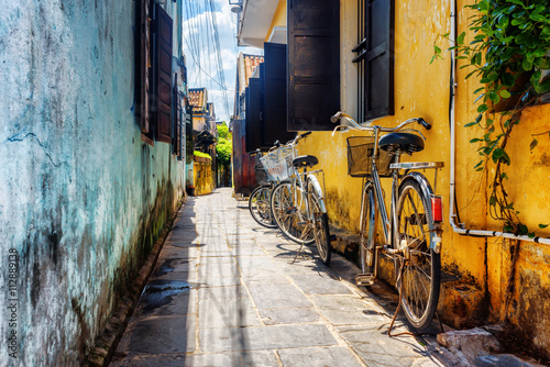 Aluminium Prints Bicycle Bicycles parked near yellow wall, Hoi An Ancient Town