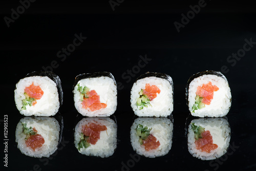 close-up of sushi with salmon and cucumber on a dark background - 112905523