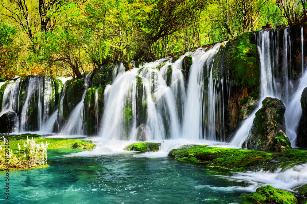 Amazing waterfall and azure lake with crystal clear water