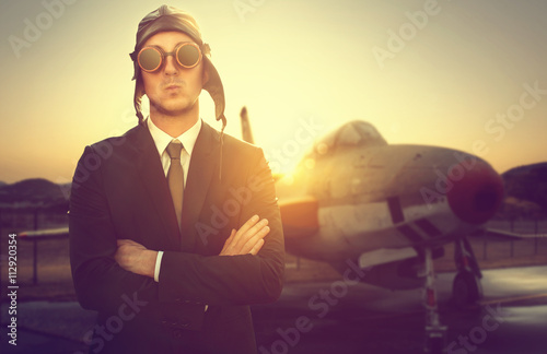 Cuadros en Lienzo Geschäftsmann mit Pilotenkappe vor altem Flugzeug