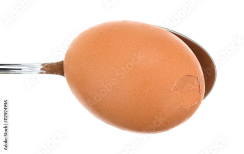 Aluminium Prints Grocery Brown egg that is cracked on a spoon top view against a white background.