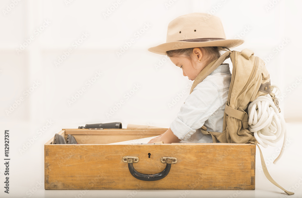 3207a13b17cb4 Photo   Art Print Adorable little girl in a safari hat and explorer clothes  reading old book sitti