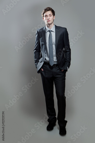 Fotografie, Obraz  Serious young business man on gray background