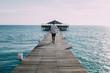 Man walking along wooden pier, rear view
