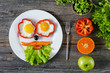 Eggs breakfast for kids. Colorful funny face on plate breakfast for children. Rustic wooden background