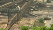 Open-cast mining. Trucks driving under flat conveyor terminal. Medium shot. Surface mine.