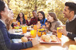 canvas print picture - Group of happy friends eat and laugh at a table at a barbecue