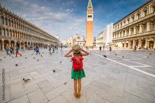 Foto  Young female traveler with hat and backpack standing on San Marco square with tower and basilica on the background in Venice
