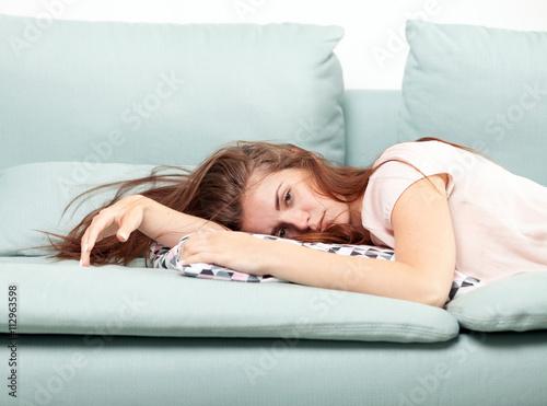 Fotomural Mujer joven agotada acostado en el sofá en casa