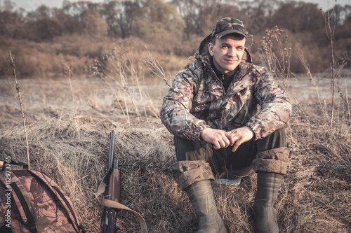 Foto op Aluminium Jacht Hunter man in rural field with shotgun and backpack during hunting season