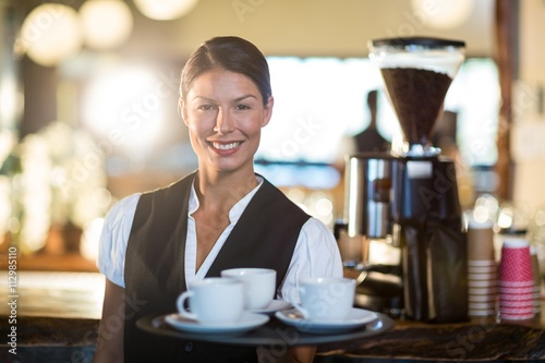 Fotografía  Portrait of waitress holding a tray with coffee cups