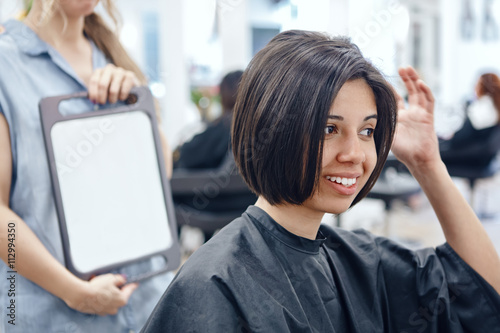 Fotomural Closeup portrait of hispanic latin girl woman sitting in chair in hair salon loo