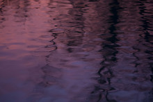 Purple Water At Sunset With Ripples And Shadows.