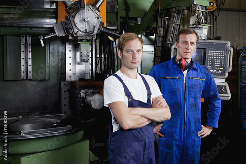 Portrait of two manual workers in a metal parts factory