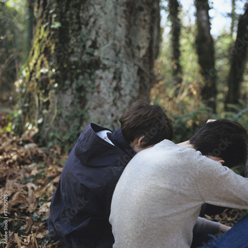 Two People Sitting Hunched Over In A Forest Buy This Stock Photo