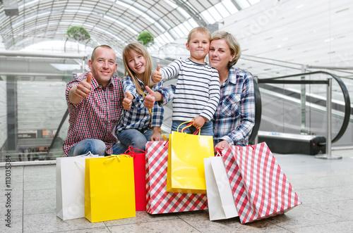 Plakat Rodzina z torba na zakupy w centrum handlowym pokazuje kciuki