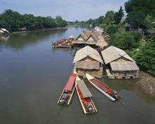 Boats Moored Near A Restaurant On The Kwai River In Thailand