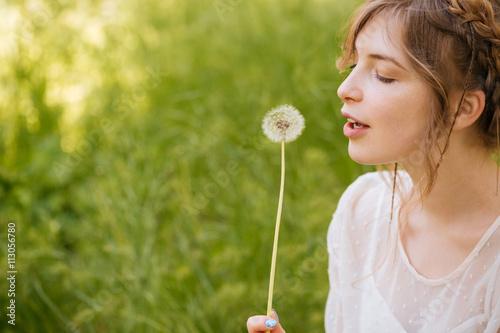 Photographie  Belle femme tenant et en soufflant sur le pissenlit extérieur