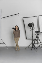 Full Length Of Mature Female Photographer With Camera In Photo Studio