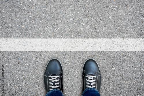 Fototapeta Black casual shoes standing at the white line obraz