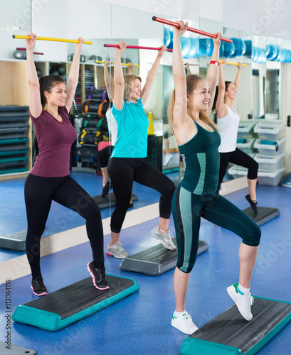 Fototapeta Females working out on aerobic step platform in modern gym obraz
