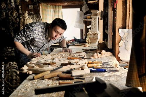 Fotografija Carver in workshop of wood carving blow off sawdust