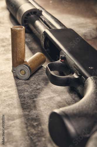 Fototapeta Weapon. Shotgun concept. Black shotgun and ammunition.