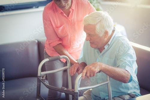 Canvastavla Senior woman helping senior man to walk with walker