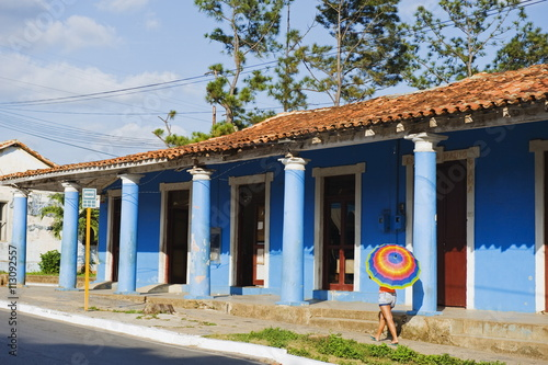 Woman with parasol walking past a colourful building, UNESCO World Heritage Site, Vinales Valley, Cuba, West Indies, Caribbean, Central America