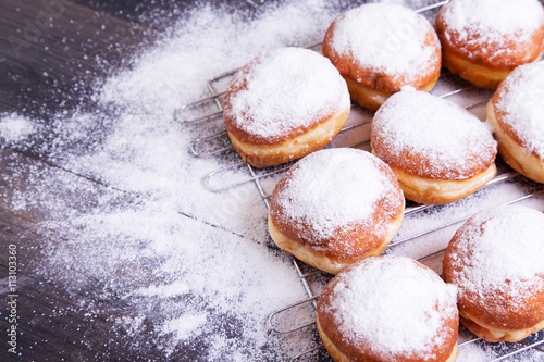 Foto German donuts - berliner with icing sugar on a dark wooden background