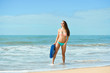 Pretty surfer young lady on the beach with bodyboarding, ready for fun