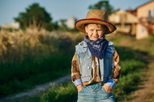 Little Boy Dressed In Western Style In The Field
