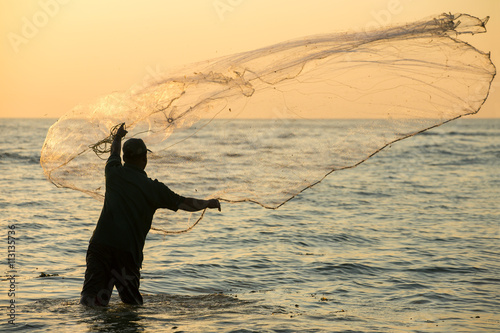 Fotografia, Obraz Silhouette of the unidentified Indian fisherman throwing net in sea on sunset in Fort Kochi, India