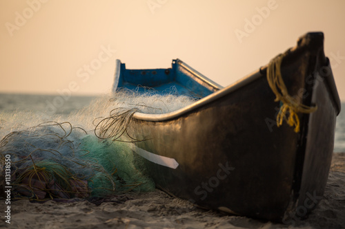 Canvas Print Fisherman boat with fishing nets on the Gokarna beach near the ocean in Karnatak