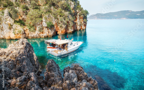 Fishing boat at mediterranean sea in cosy bay. Wallpaper Mural